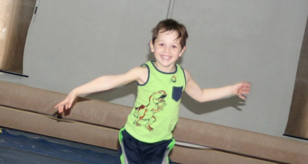 smiling young boy jumping