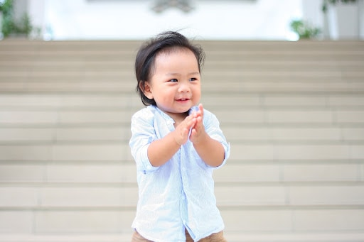toddler boy smiling and clapping