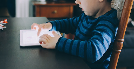young boy using AAC device tablet